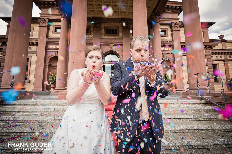 Brautpaar pustet Konfetti