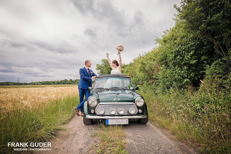 Braut steht im Auto und schaut durchs Schiebedach