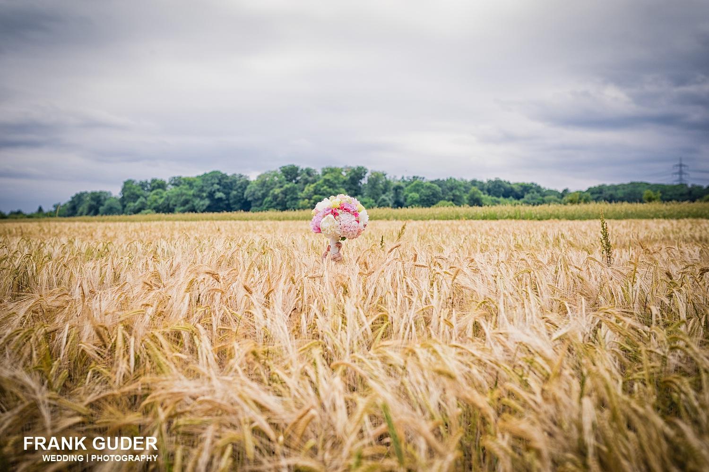 Brautstrauss schaut aus Kornfeld