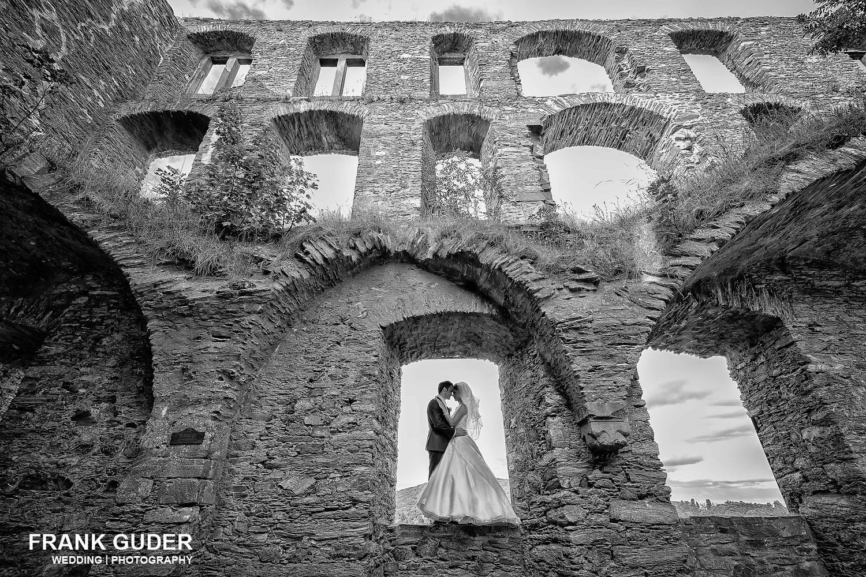 Brautpaar steht im Fenster einer Burg