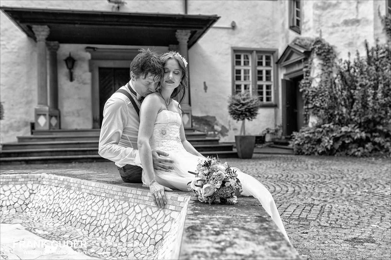 Brautpaar sitzt auf Brunnen